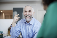 Smiling businessman gesturing while discussing female colleague at desk - MASF08890