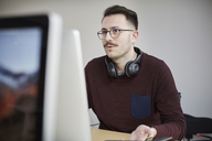 Businessman wearing headphones while using laptop at desk in office - MASF08899