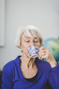Senior woman with eyes closed having drink in nursing home - MASF08908