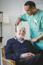 Mature male caregiver combing hair of senior man sitting on chair in nursing home - MASF08911