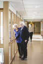 Senior couple talking while standing by window in corridor at nursing home - MASF08914