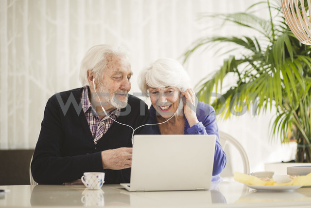 Cheerful senior couple using in-ear headphones while video calling through laptop in nursing home - MASF08917