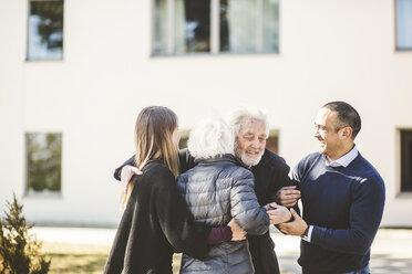 Happy multi-generation family embracing outside nursing home - MASF08929