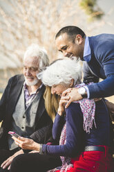 Cheerful multi-generation family looking at mobile phone outdoors - MASF08935
