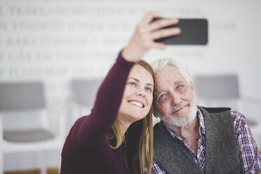 Smiling young woman taking selfie with grandfather while sitting in nursing home - MASF08944