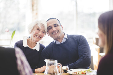 Smiling senior woman sitting with son while having lunch at table in nursing home - MASF08947