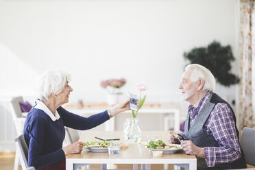 Senior woman showing mobile phone to man while having lunch in nursing home - MASF08950