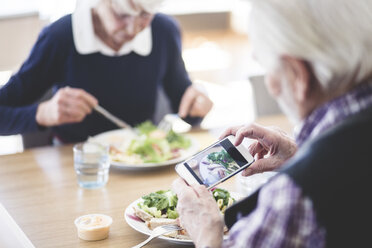 Senior man photographing food using smart phone while having lunch with woman at table - MASF08953