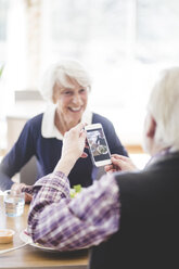 Senior man holding mobile phone while sitting with cheerful woman at table in nursing home - MASF08956