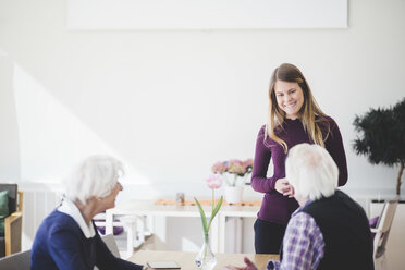 Granddaughter smiling while talking with grandparents sitting at table in nursing home - MASF08959