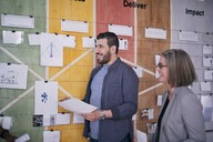 Smiling male and female business professionals holding documents while standing by notes on wall - MASF08965