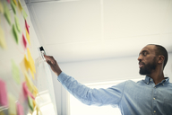 Low angle view of male engineer reading adhesive notes stuck on whiteboard in office - MASF08995