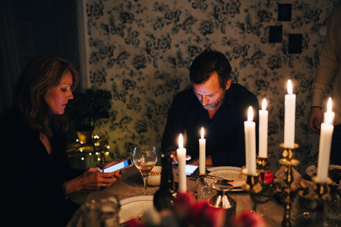 Male and female mature friends using smart phone at dining table in dinner party - MASF09022