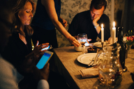 Mature friends using mobile phones while sitting at dining table in dinner party - MASF09025
