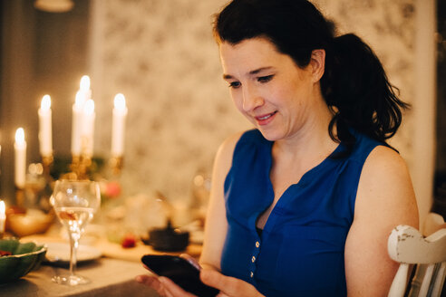 Smiling mature woman using mobile phone at dining table in dinner party - MASF09028