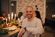 Portrait of mature man with friends at dining table in dinner party - MASF09031