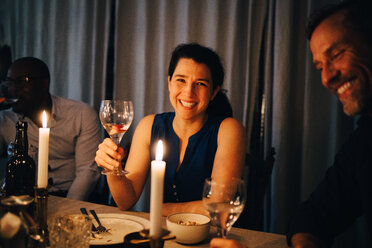 Happy woman enjoying dinner with male friends in party at home - MASF09034