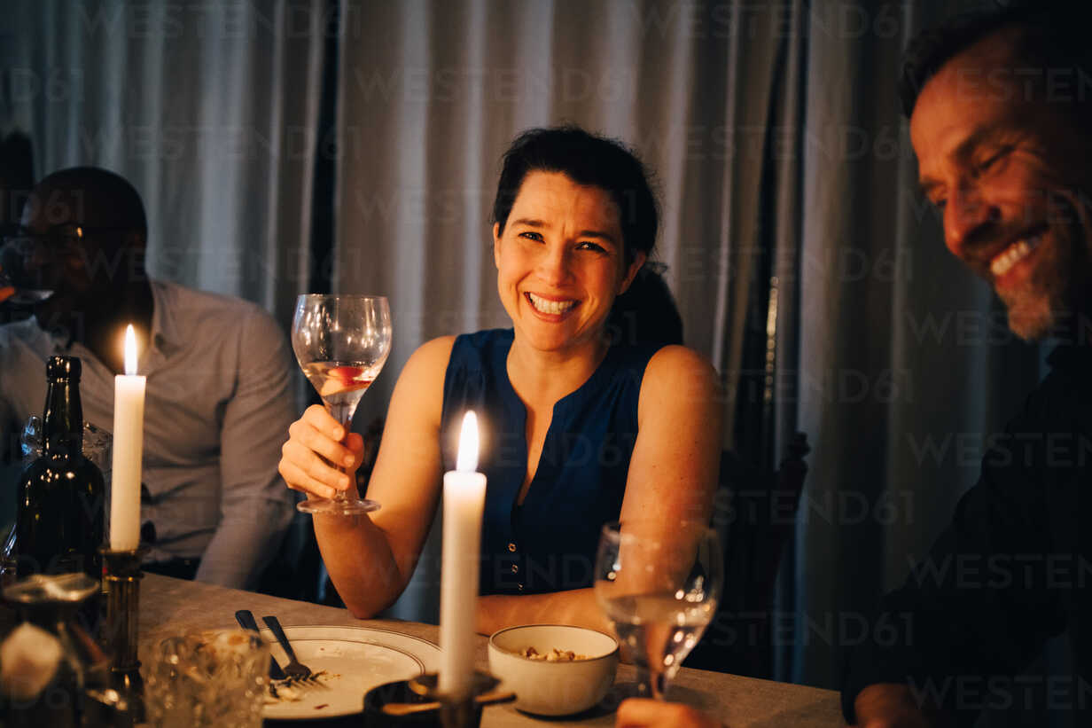 Happy woman enjoying dinner with male friends in party at home - MASF09034 - Maskot ./Westend61