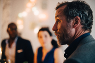 Close-up of mature man talking in dinner party with friends in background - MASF09043