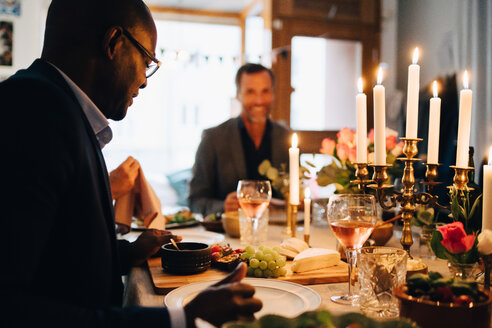Mature man having dinner with friends at dining table in dinner party - MASF09046