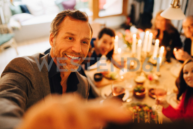 Mature man taking selfie with friends at dinner party - MASF09052