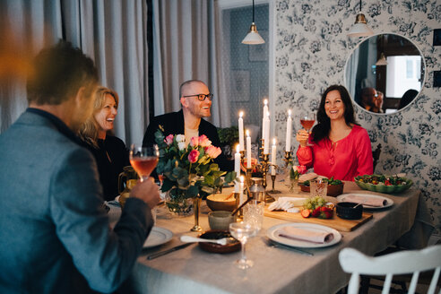 Mature male and female friends enjoying dinner party at home - MASF09055