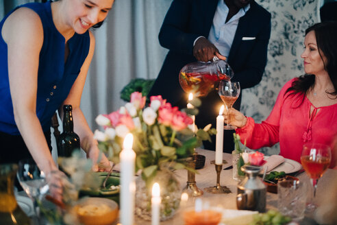 Midsection of man pouring drink to friend at dining table in party - MASF09064