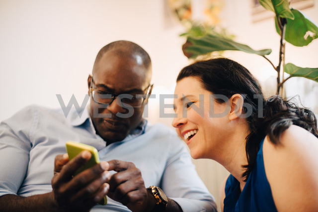 Mature man showing mobile phone to smiling friend at party - MASF09073