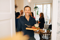Portrait of smiling man with serving tray standing against friends in party at home - MASF09076