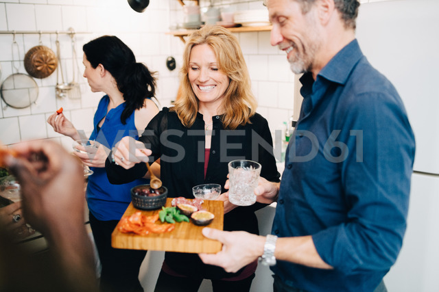 Smiling mature friends enjoying food and drinks in dinner party at home - MASF09085