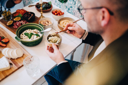 High angle view of man having food at table during dinner party - MASF09103