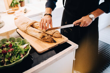 Midsection of man cutting bread by salad at kitchen counter - MASF09106