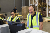Confident senior male customer service representative talking through headset while standing by coworker in distribution - MASF09115
