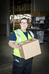 Portrait of confident mature female worker holding cardboard box while standing at distribution warehouse - MASF09127