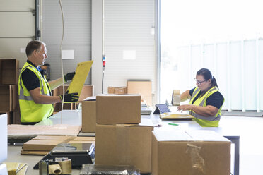 Coworkers packing merchandise on desk at distribution warehouse - MASF09133