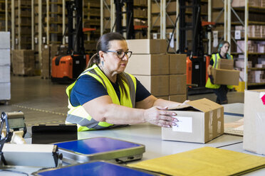 Mature female worker holding cardboard box at desk in distribution warehouse - MASF09136