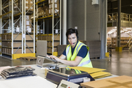 Confident young male customer service representative using laptop while sitting at desk in warehouse - MASF09139