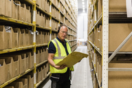 Senior male worker looking at package while talking through headset standing amidst racks at distribution warehouse - MASF09145
