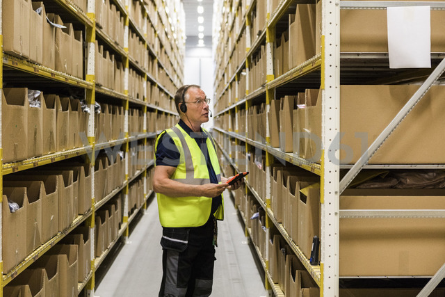 Side view of senior male worker with digital tablet looking at packages on rack while talking through headset at distrib - MASF09148