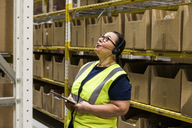 Mature female worker with digital tablet looking up while talking on headset against rack at distribution warehouse - MASF09151