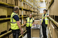 Multi-ethnic coworkers discussing while standing with cart on aisle amidst racks at distribution warehouse - MASF09169
