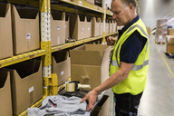 Side view of senior male worker packing merchandise in cardboard box at distribution warehouse - MASF09175