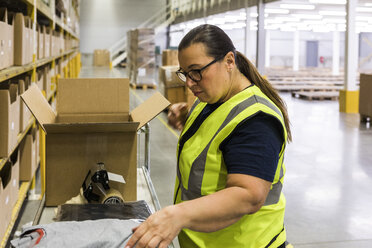 Side view of female worker packing cardboard box at warehouse - MASF09178