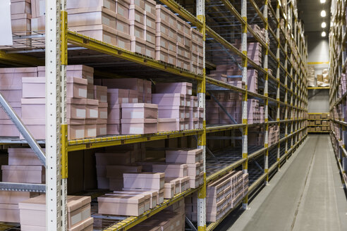 Packages on racks by narrow empty aisle at distribution warehouse - MASF09181