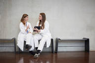 Full length of confident female doctors discussing over digital tablet while sitting against wall at hospital - MASF09205
