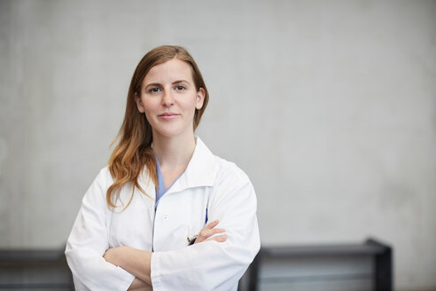 Portrait of confident mid adult female doctor standing with arms crossed against wall at hospital - MASF09208