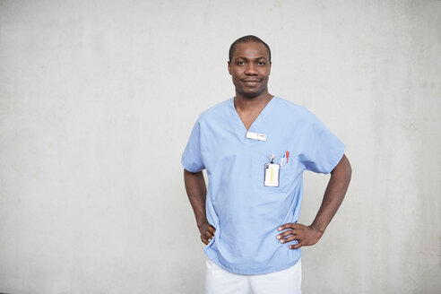 Portrait of confident mid adult male nurse standing with hands on hips in corridor at hospital - MASF09211