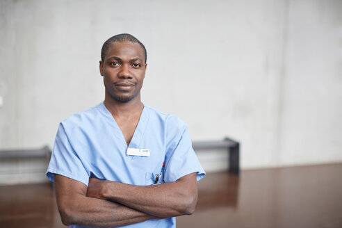 Portrait of confident mid adult male nurse standing with arms crossed in corridor at hospital - MASF09217