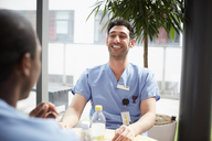 Smiling young male nurse talking with mid adult coworker against window at cafeteria in hospital - MASF09232
