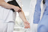 Midsection of male nurse gesturing while standing with coworkers at hospital - MASF09259